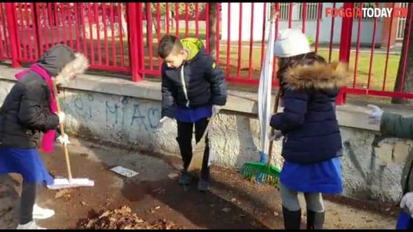 Armati di scope e rastrelli ripuliscono i marciapiedi adiacenti la scuola: l'esempio dei piccoli alunni della 'Leopardi'